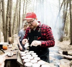 Tyler Scott, chef and co-owner of Rare in downtown Peterborough, prepares food outdoors for a public event in 2019. During the COVID-19 Pandemic, Rare and a number of other local restaurants have established safe food delivery and takeout options. The DBIA has a list of local eateries offering this type of service: https://downtownptbo.ca/news-item/eateries-available-for-take-out-delivery.
